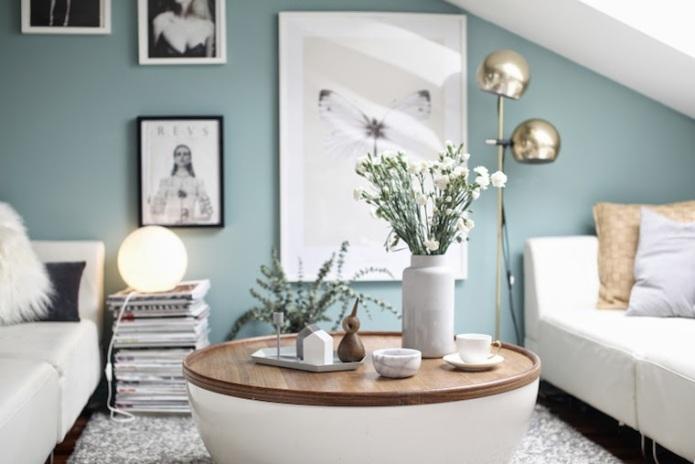 salón con pared pintada de azul grisaceo, sofás blancos y cojines color mostaza